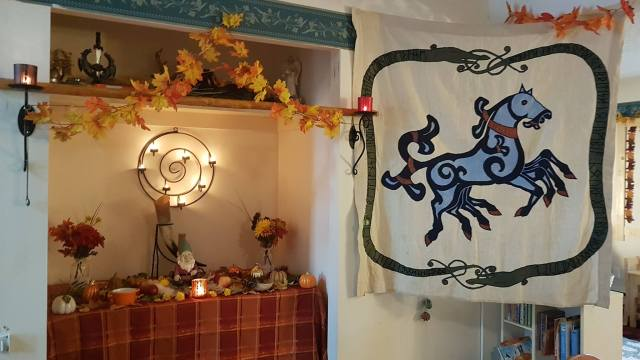 On left, an altar prepared to honour the elves/landwights during a May Day faining. On right, the Freehold banner.